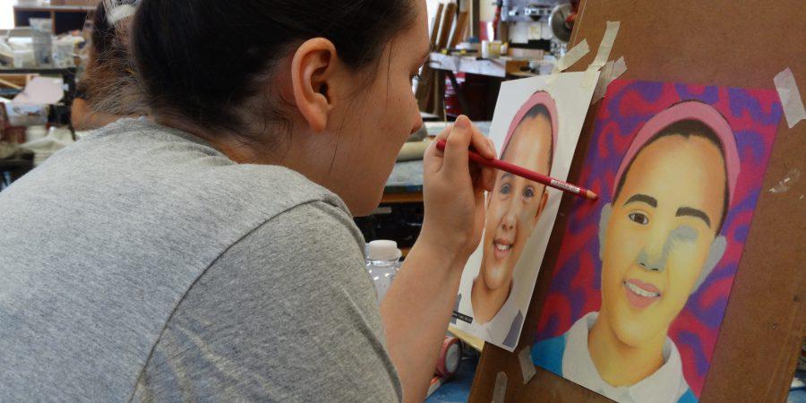 Student painting a portrait