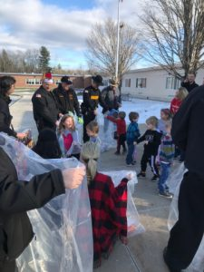 Helpers collect toys from students