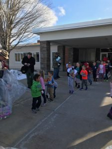 Students line up to drop off their toys