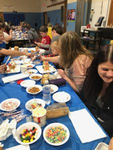 Students and parent make Gingerbread houses