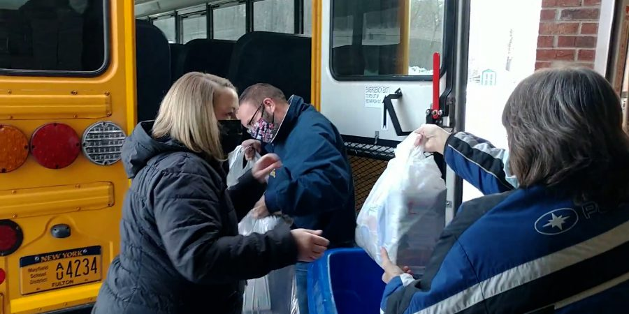 Mayfield transportation employees loading food bags onto a bus