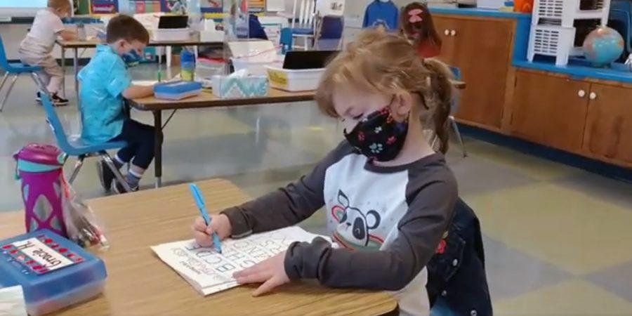 Kindergarten student sitting in class wearing mask