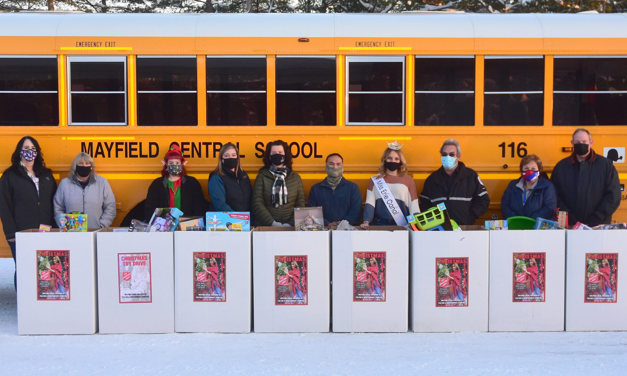 Transportation staff lined up with toys in front of a Mayfield bus