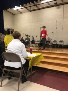 Student speaks into microphone during bee