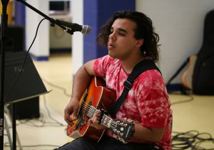 Student plays guitar at the coffeehouse