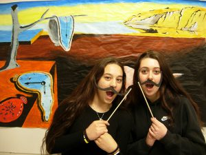 Students acting out in front of dali painting
