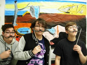 Students have fun in front of the painting