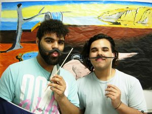 Students show off mustaches in front of painting