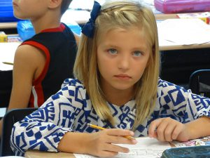 Student in blue top writing in class