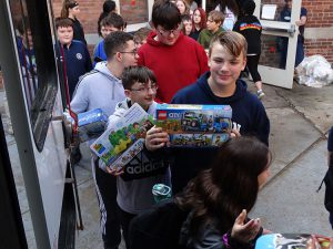 Students bringing gifts to the bus