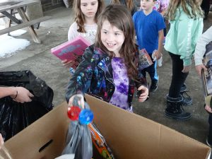 Student smiles as she drops gift in box