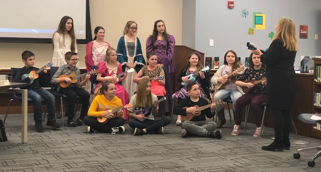 Students playing ukuleles at the Board of Education meeting