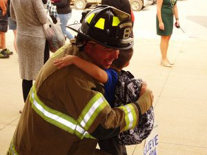 Student hugging a firefighter