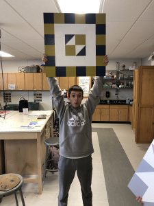 Student holding up project