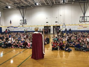 Principal dressed as a queen addresses the assembly