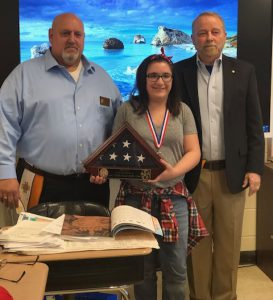 Student with VFW officials handing her a flag