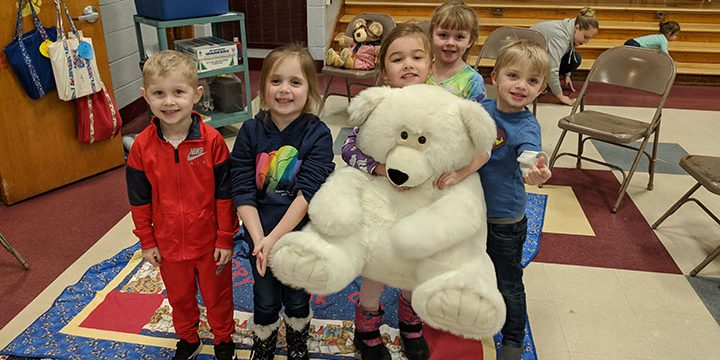 Students holding large teddy bear in the cafeteria